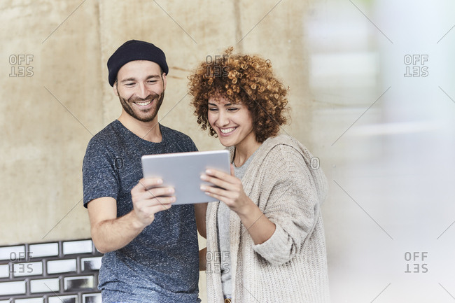 Happy man and woman sharing tablet