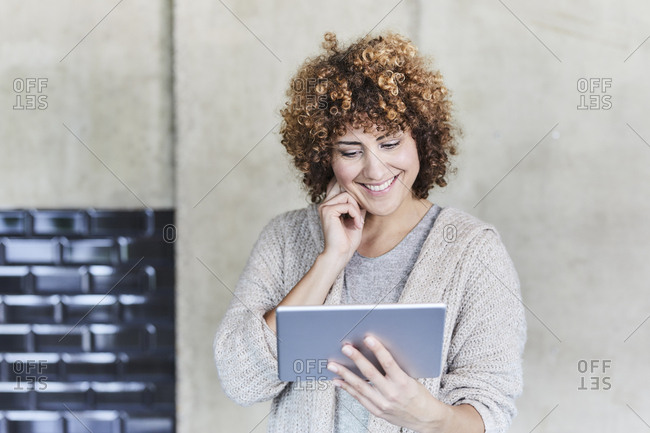 Smiling woman using tablet at concrete wall