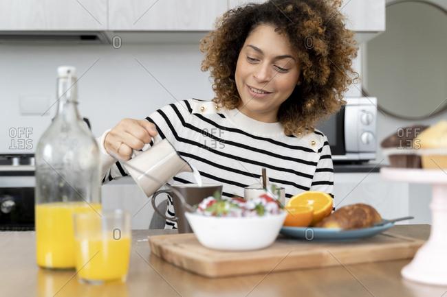 Woman sitting in kitchen- having breakfast