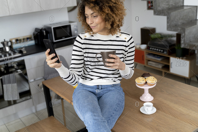 Woman sitting at home- using smartphone- eating muffin
