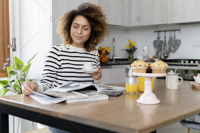 Woman sitting in kitchen- reading magazines and drinking coffee