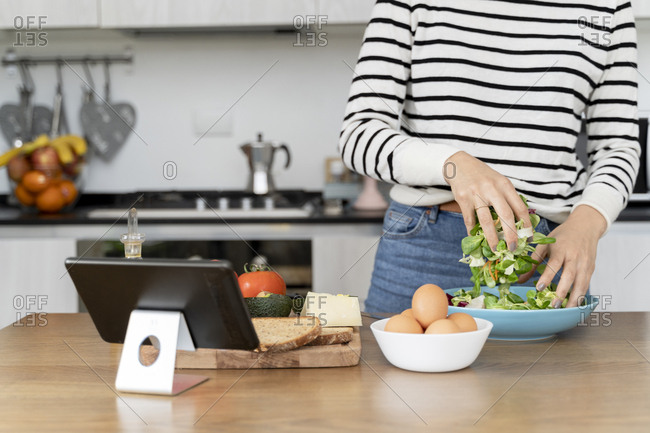Woman standing in kitchen- preparing salad for lunch