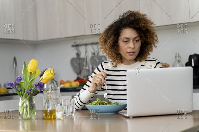 Woman using laptop- eating salad for lunch