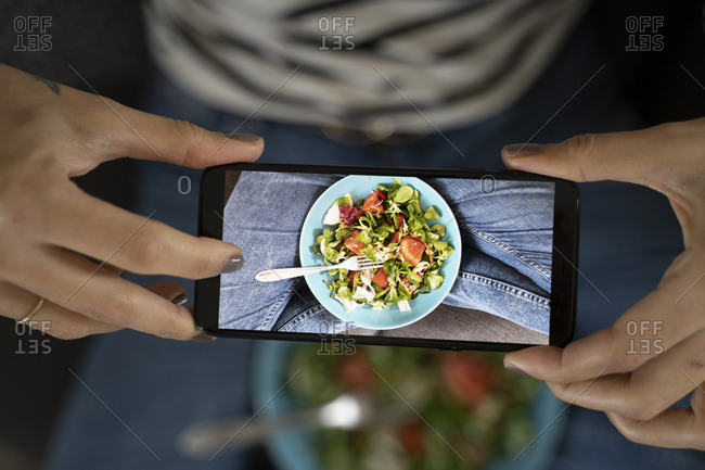 Woman's hands holding smartphone- taking picture of salad
