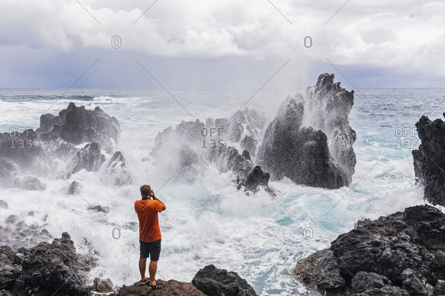 USA- Hawaii- Big Island- Laupahoehoe Beach Park-Man taking pictures of breaking surf at the rocky coast
