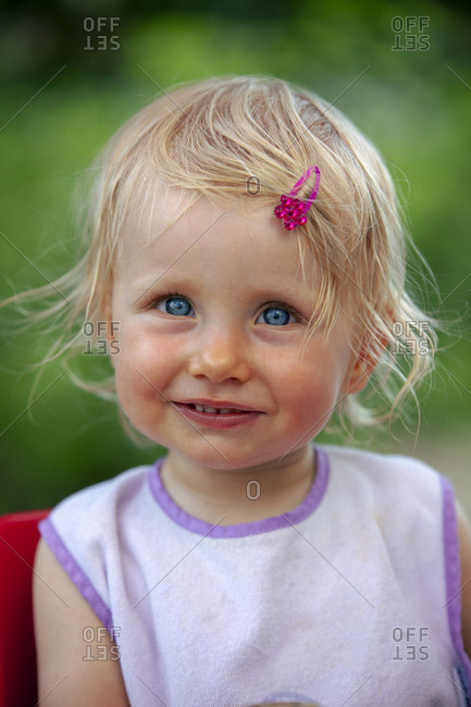 Portrait of blond little girl with bib and pink haipin