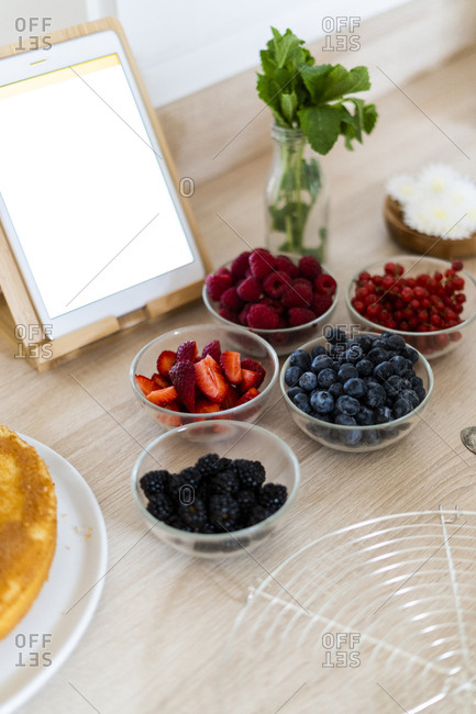 Tablet and fresh fruits in bowls for preparing a cake