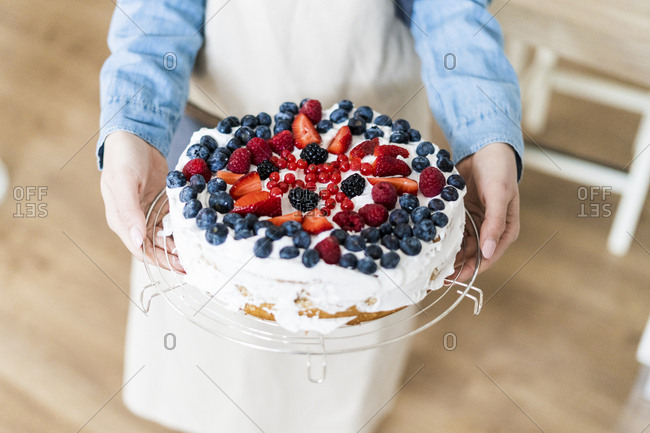 Young woman showing a cream cake with fresh fruits