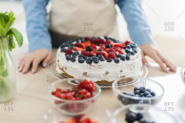 Young woman preparing a cream cake with fresh fruits