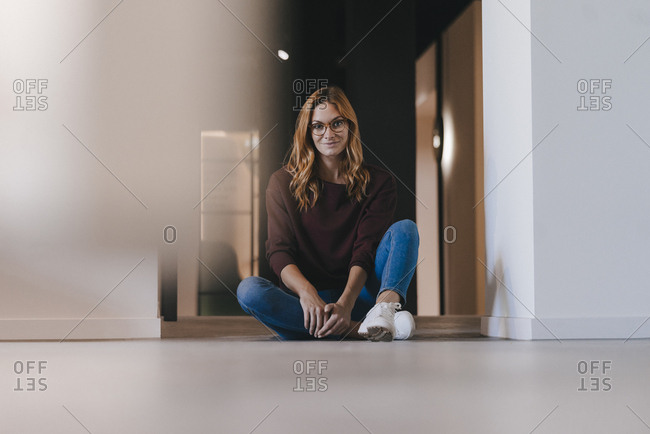 Portrait of smiling businesswoman sitting on the floor