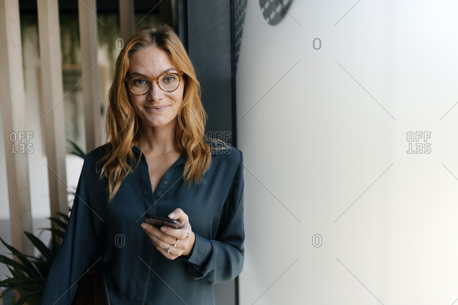 Portrait of confident businesswoman holding cell phone