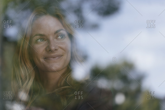 Smiling young woman behind windowpane