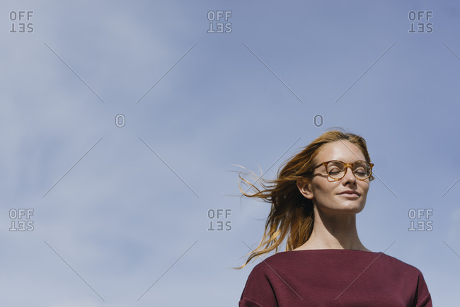 Portrait of young woman with glasses and closed eyes under blue sky