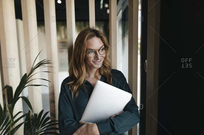 Smiling businesswoman holding laptop looking sideways