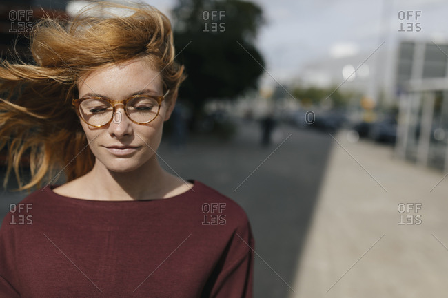Portrait of young woman with glasses and closed eyes