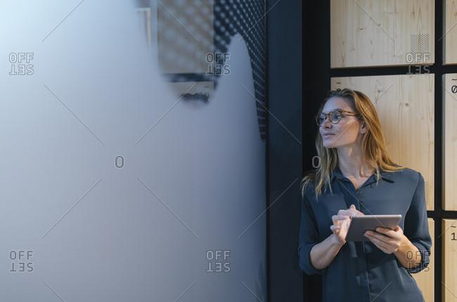 Businesswoman holding tablet looking sideways