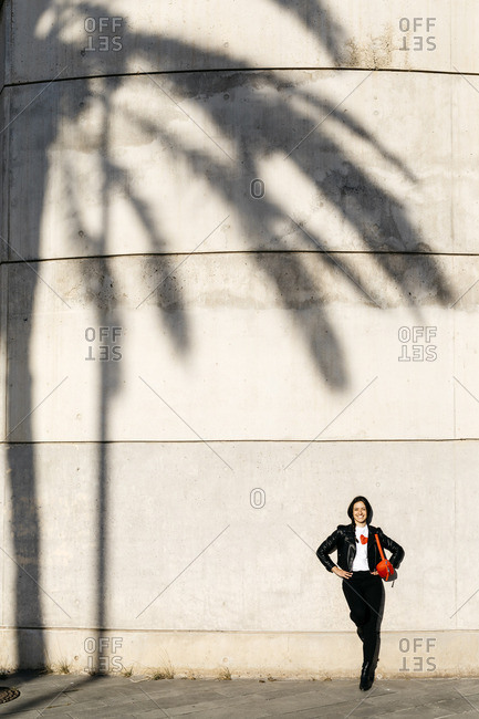 Happy young woman with a red hip bag resting on a wall with the shadow of a palm tree.