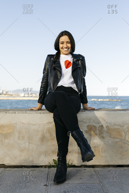 Young woman sitting on a wall- sea in the background