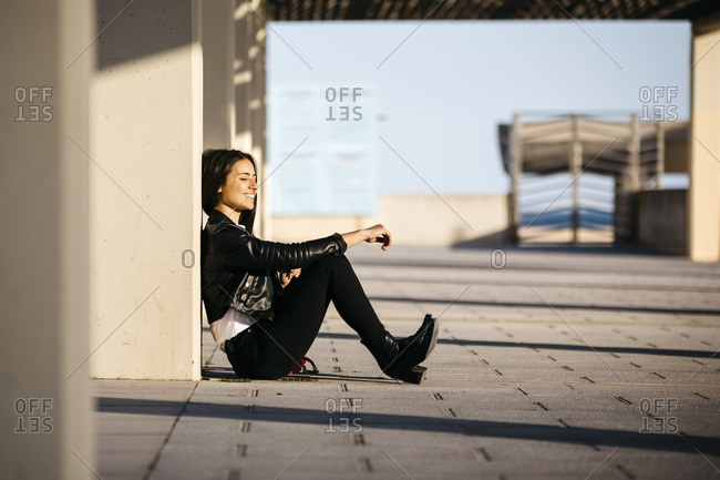 Young woman sitting on floor- enjoying sunlight