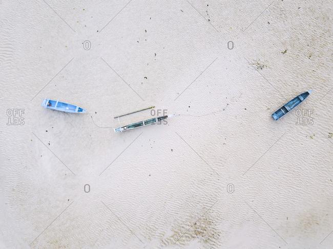 Indonesia- Sumbawa- Kertasari- Aerial view of blue boats at the beach