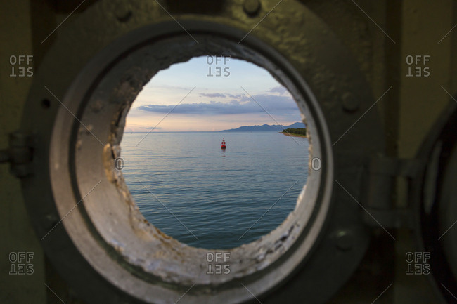 Indonesia- View at Lombok coastline in porthole of ferry
