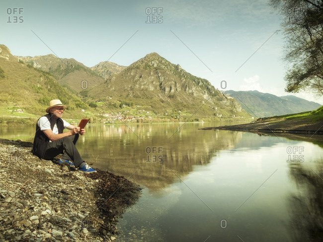 Italy- Anfo- senior man sitting at Lake Idro using tablet