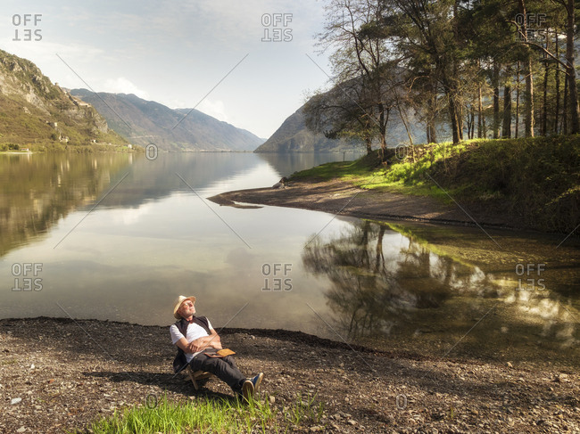 Italy- Lombardy- senior man relaxing at Lake Idro