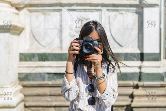 Italy- Florence- young tourist taking photograph with camera