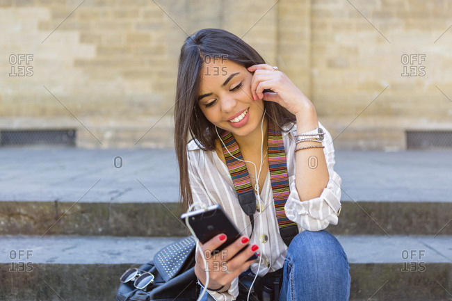 Italy- Florence- portrait of young tourist sitting on stairs listening music with earphones and smartphone