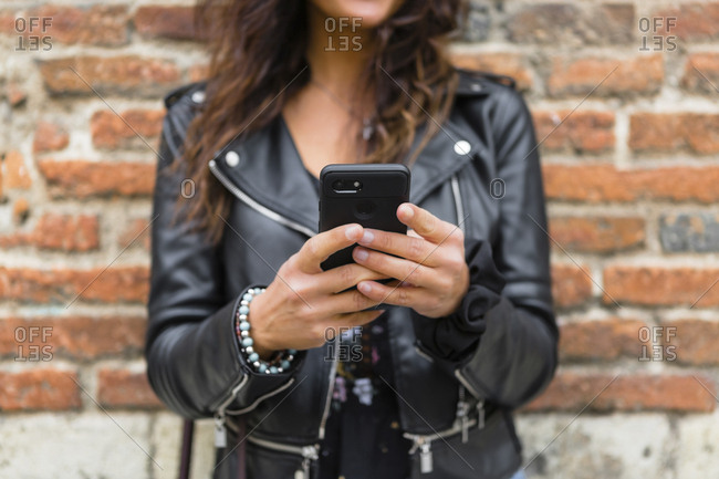 Young woman wearing black leather jacket- using smartphone- brick wall in the background