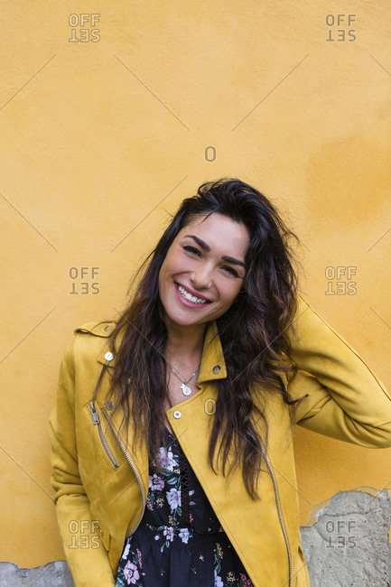 Portrait of young woman wearing yellow leather jacket- hand in hair