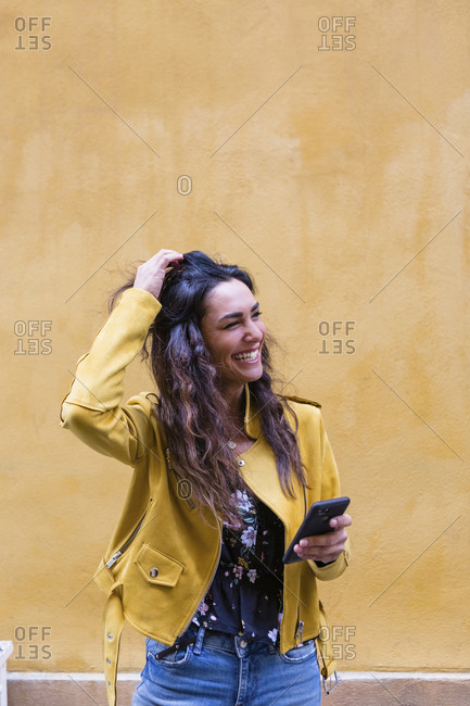 Portrait of young laughing woman wearing yellow leather jacket and holding smartphone