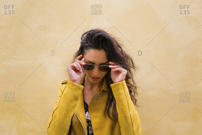 Portrait of young woman wearing yellow leather jacket and sun glasses