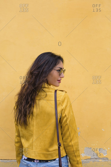 Portrait of young woman wearing yellow leather jacket and sun glasses- rear view