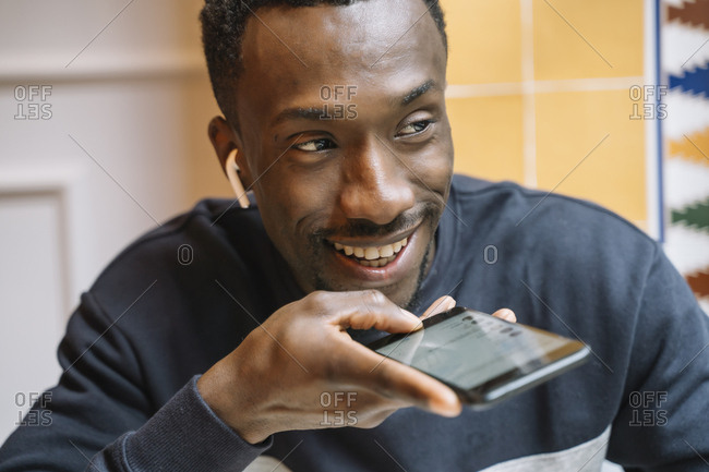 Portrait of smiling young man with wireless earphones on the phone