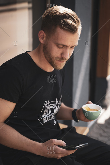 Young man drinking coffee and using mobile phone in coffee shop
