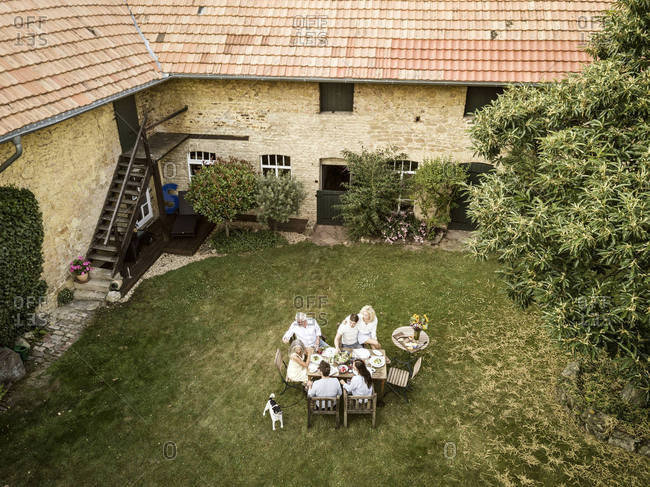 Family eating together in the garden in summer