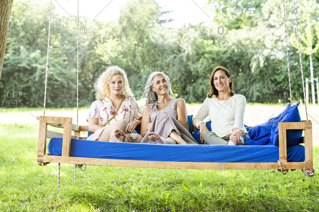 Women of a family relaxing in garden- sitting on a swing bed