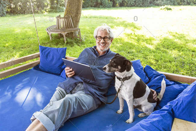 Senior man relaxing on a swing bed in his garden- using digital tablet