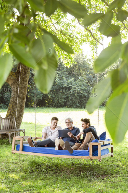Men of a family sitting on a swing bed ing the garden- talking- using digital tablet