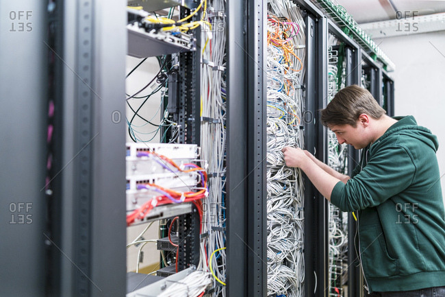 Teenager working with cables in server room