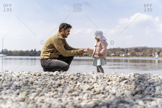 Germany- Bavaria- Herrsching- father and daughter on pebble beach at lakeshore
