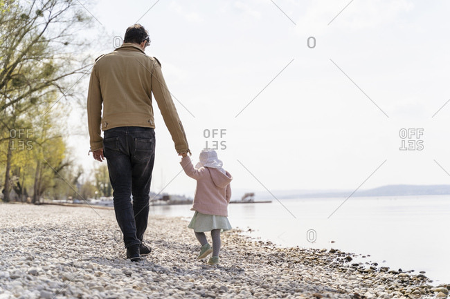 Germany- Bavaria- Herrsching- father and daughter walking on pebble beach at lakeshore