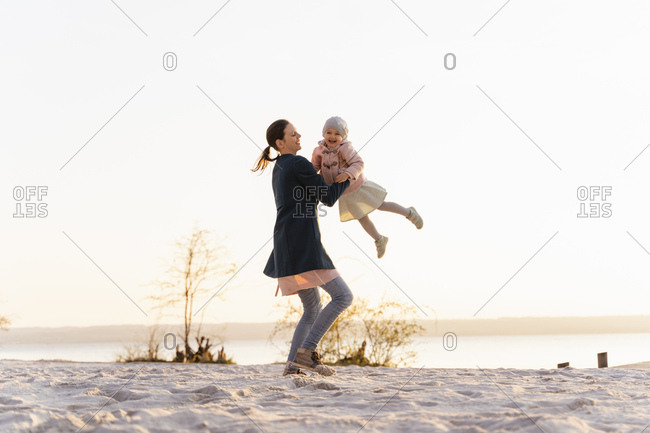 Germany- Bavaria- Herrsching- mother carrying daughter at the lakeshore at sunset