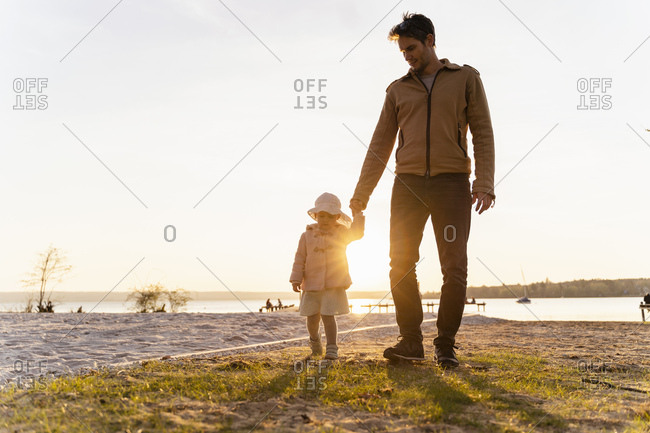 Germany- Bavaria- Herrsching- father and daughter walking at the lakeshore at sunset