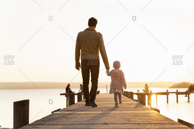 Germany- Bavaria- Herrsching- father and daughter walking on jetty at sunset