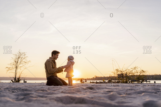 Germany- Bavaria- Herrsching- father and daughter playing on the beach at sunset