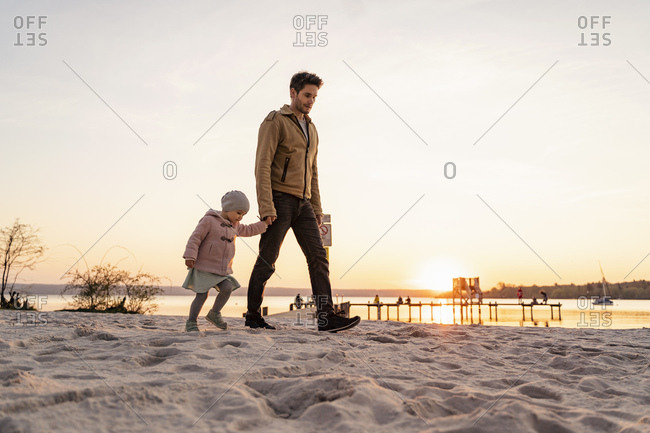 Germany- Bavaria- Herrsching- father and daughter walking on the beach at sunset