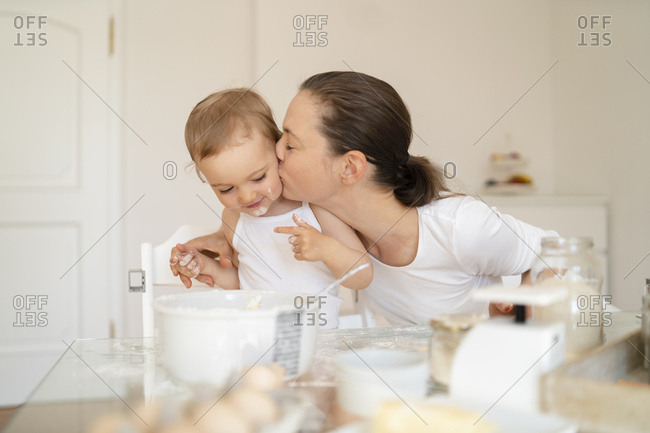 Mother kissing little daughter while making a cake together in kitchen at home