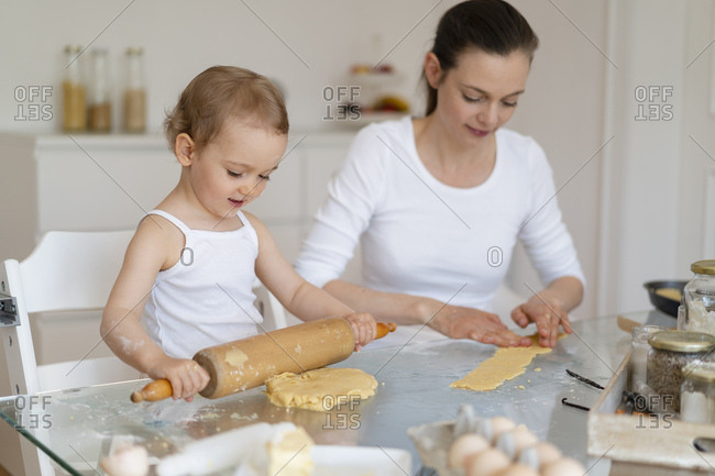 Mother and little daughter with dough roll making a cake together in kitchen at home